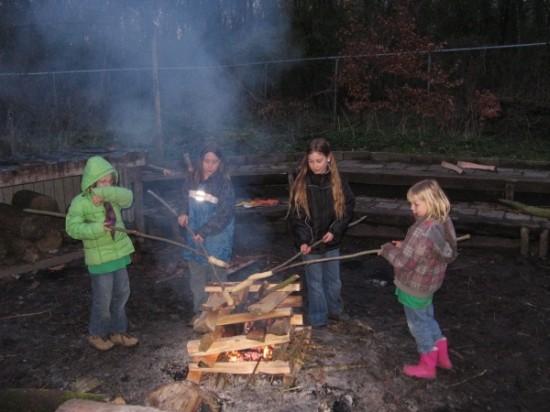 De kabouters bakken een broodje boven het kampvuur.
